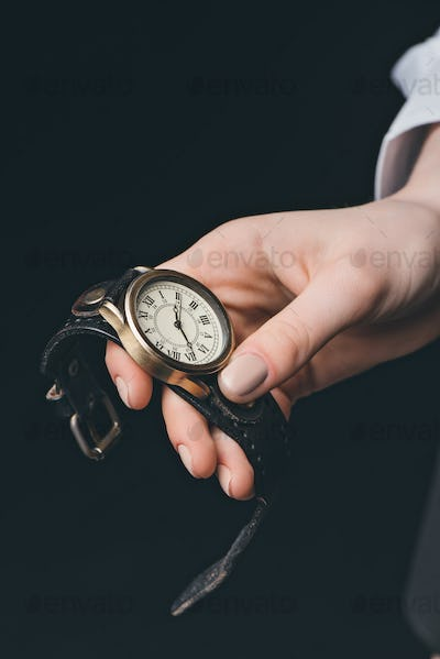 Close-up of female hand holding vintage watch, studio shot