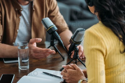 cropped view of two radio hosts recording podcast in broadcasting studio