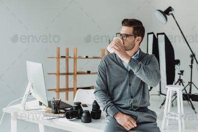 handsome male photographer drinking coffee in modern office