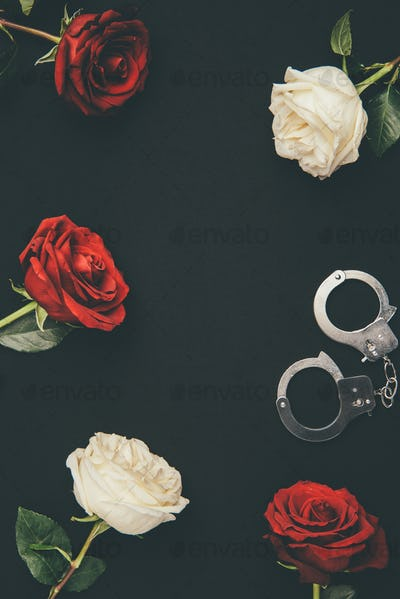 Metal handcuffs with rose flowers isolated on black