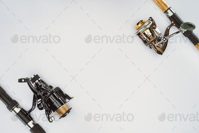 view from above of two arranged fishing rods isolated on white, minimalistic concept