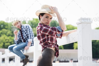 cowboy style girl posing and looking at camera near fence on ranch