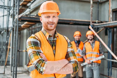 smiling builder standing at construction site with crossed arms while his colleagues standing