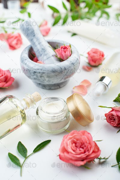 Handmade rose cosmetics concept of mortar and pestle with rose buds with dropper