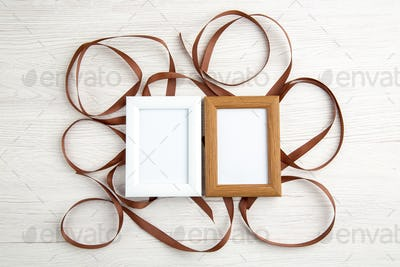 Top view of small empty wooden picture frames around ribbon on white background