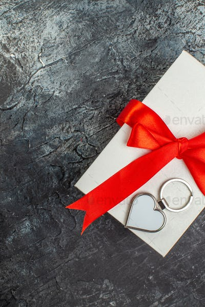 Half shot of beautifully packaged gift boxes tied with red ribbon on the right side on dark