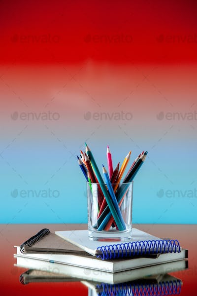 Vertical view of colored pencils kept in a glass jar on stacked spiral notebooks on mixed color