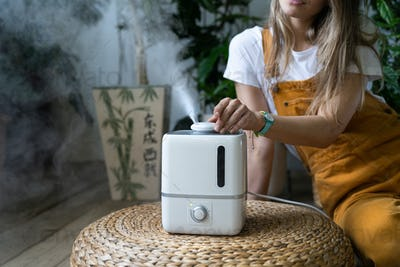 Girl feeling fresh sitting on wooden floor using air humidifier in home garden during heating period