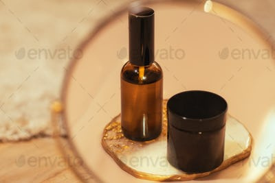 Brown glass cosmetic bottle on warm nude  in the miror