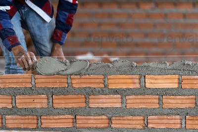 Closeup hand professional construction worker laying bricks in new industrial site.