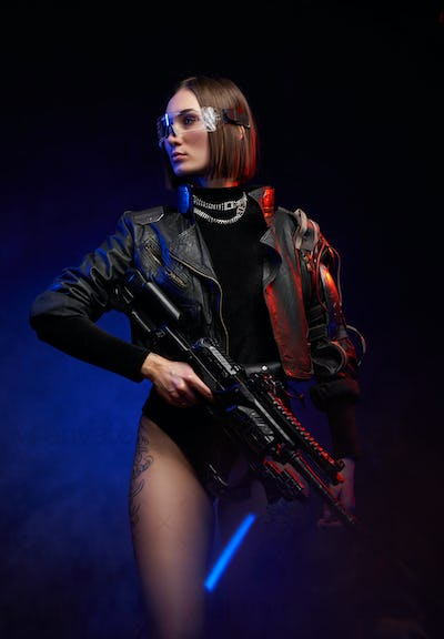 Military woman with eyewear and rifle posing in dark background