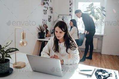Joyful female person looks at laptop sitting at desktop in office