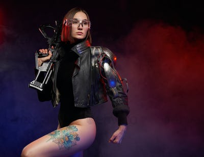 Woman with cybernetic arm poses with rifle in dark background