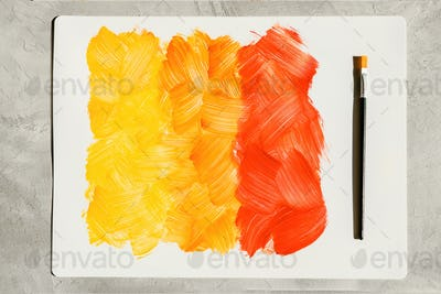 Action painting. Abstract Hand-painted yellow and orange art background. Multicolored paint strokes