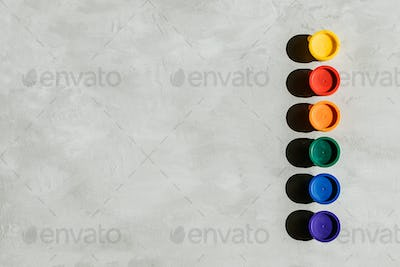 Action painting, trend art background. Multicolored paints in round jars and brush on a gray