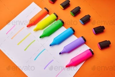 Colorful permanent markers on paper sheet