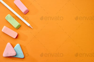 Pencil, rubbers and chalk, orange background