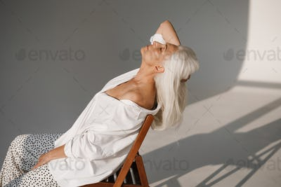 Pleased elderly white-haired woman posing while sitting on chair