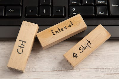 bottom view ctrl enter shift icons on wood blocks on keyboard on wooden table