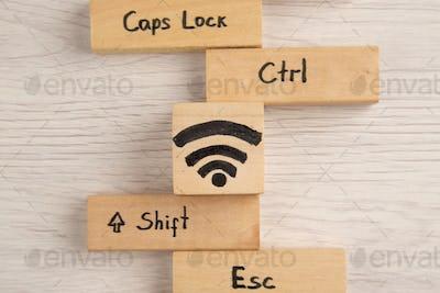 top view wifi shift caps lock ctrl esc icons on wood blocks on table