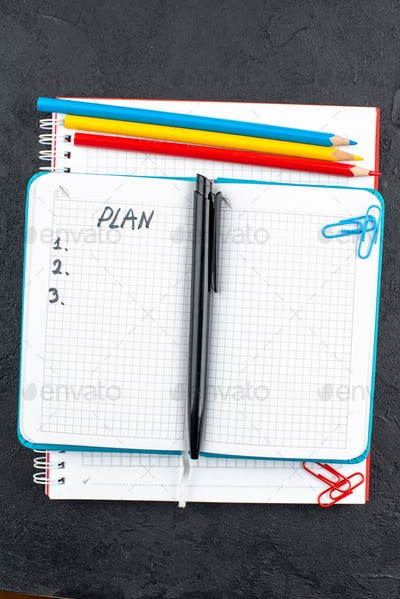 top view office stuffs plan written on notepad red yellow and blue pencils black pen on table