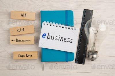 top view ebusiness written on small notepad on blue notebook ruler light bulb alt ctrl backspace