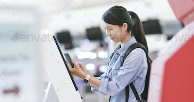 Woman using machine for check in the airport