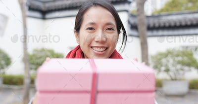 Woman giving a present for young, wish young a have a happy new year