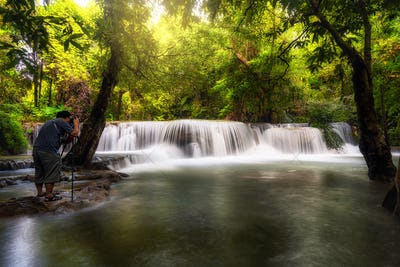 Photographer taking photo scene of Beautiful waterfall in the deep forest,Pha Tat Waterfall