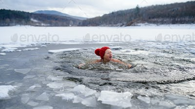 Front view of active senior woman in swimsuit outdoors in water in winter, cold therapy concept.