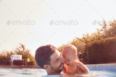 Father With Baby Daughter Having Fun On Summer Vacation Splashing In Outdoor Swimming Pool