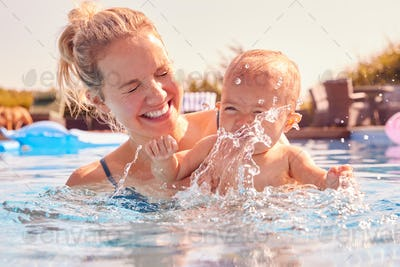 Mother With Baby Daughter Having Fun On Summer Vacation Splashing In Outdoor Swimming Pool
