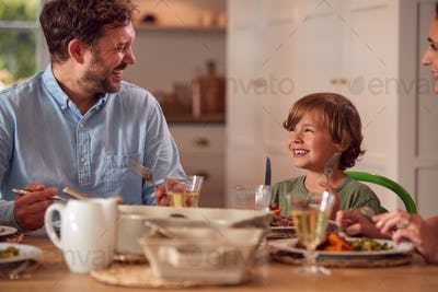 Family Sitting Around Table At Home Enjoying Meal Together