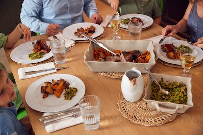 Close Up Of Family Sitting Around Table At Home Enjoying Meal Together
