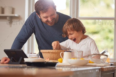 Father And Son In Pyjamas Making Pancakes In Kitchen At Home Following Recipe On Digital Tablet