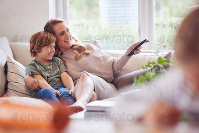 Mother Relaxing With Children On Sofa At Home Watching TV Together