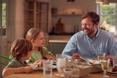 Father And Children Sitting Around Table At Home Enjoying Meal Together
