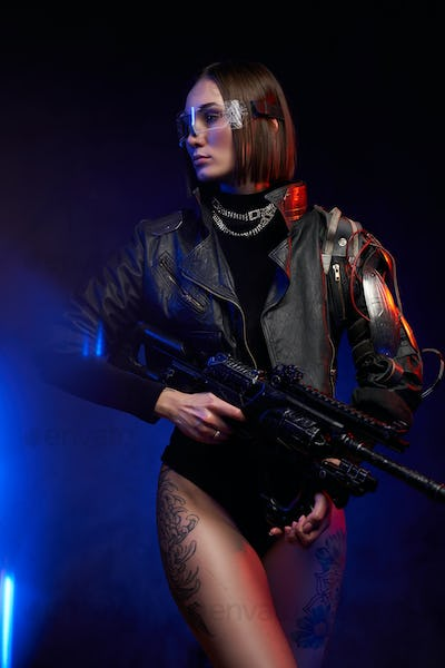 Cyber woman with rifle posing in dark background with lights
