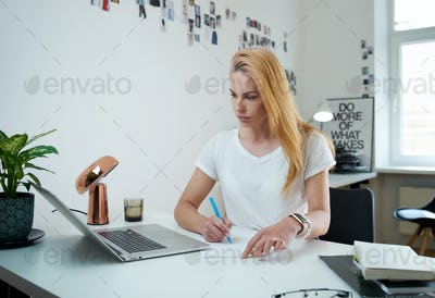 Woman freelancer writes document with a pencil sitting at table