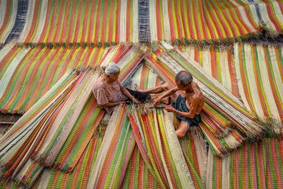 Top view of old Vietnamese lover craftsman making the traditional vietnam mats with happiness