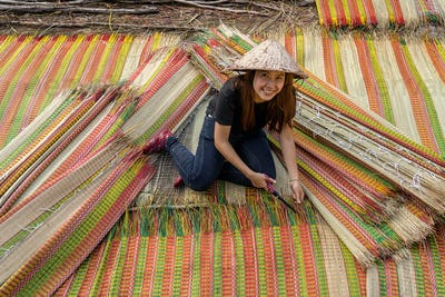 Top view of young Vietnamese craftsman making the traditional vietnam mats with happiness