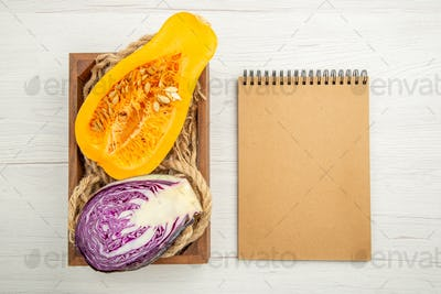 top view butternut squash and red cabbage cut in half rope in wooden box notebook on grey background