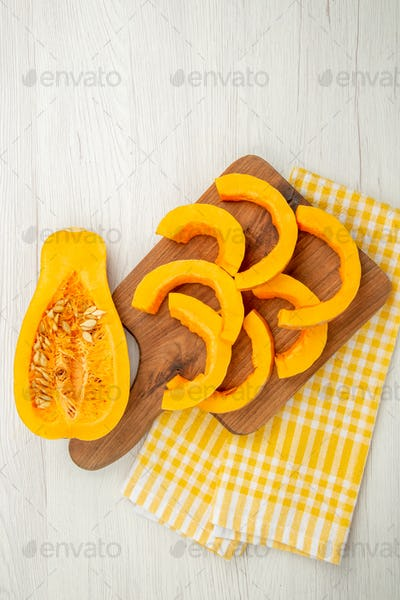top view chopped butternut squash on chopping board on yellow and white checkered kitchen towel on