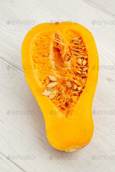 top view butternut squash cut in half on white wooden background