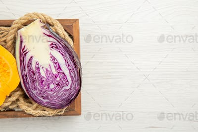top half view butternut squash and red cabbage cut in half rope in wooden box on grey background