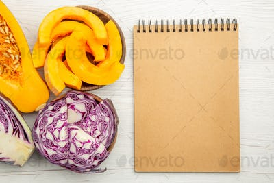 top view half butternut squash half red cabbage squash and red cabbage slices in bowls notepad on