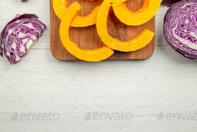 top view half chopped red cabbage butternut squash cut in half chopped squash on cutting board on