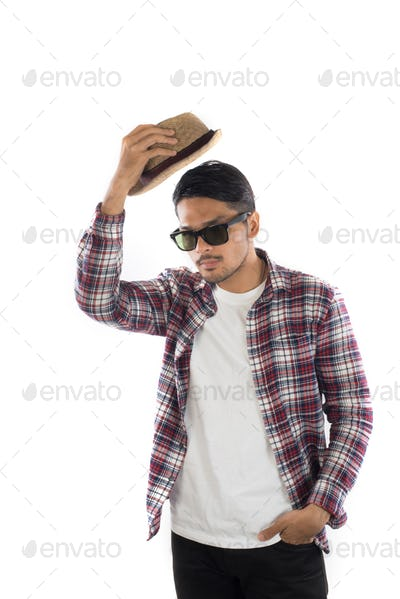 Young hipster man adjusting hat with head at camera on isolated over white studio background.