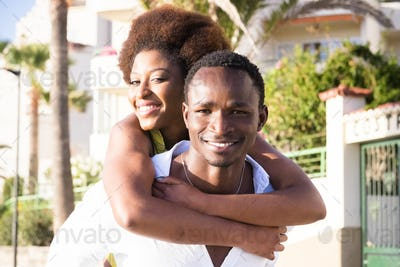 Couple of black young man and woman enjoy and smile together in piggyback carrying friends