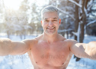 Positive senior man with bare chest taking selfie at snowy winter forest. Acclimation concept